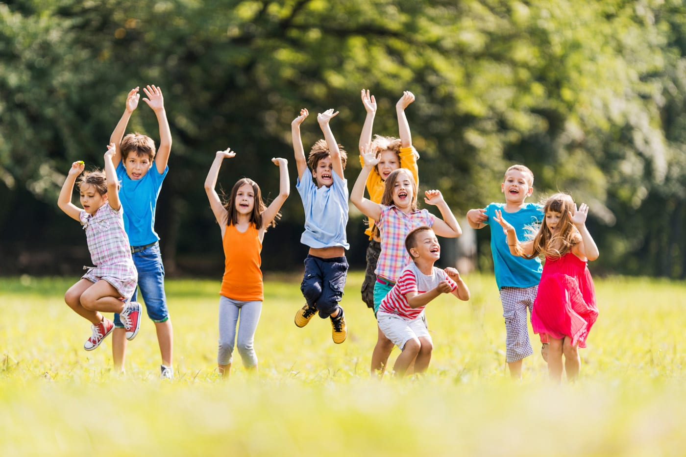 Large group of children jumping in the park and having fun.