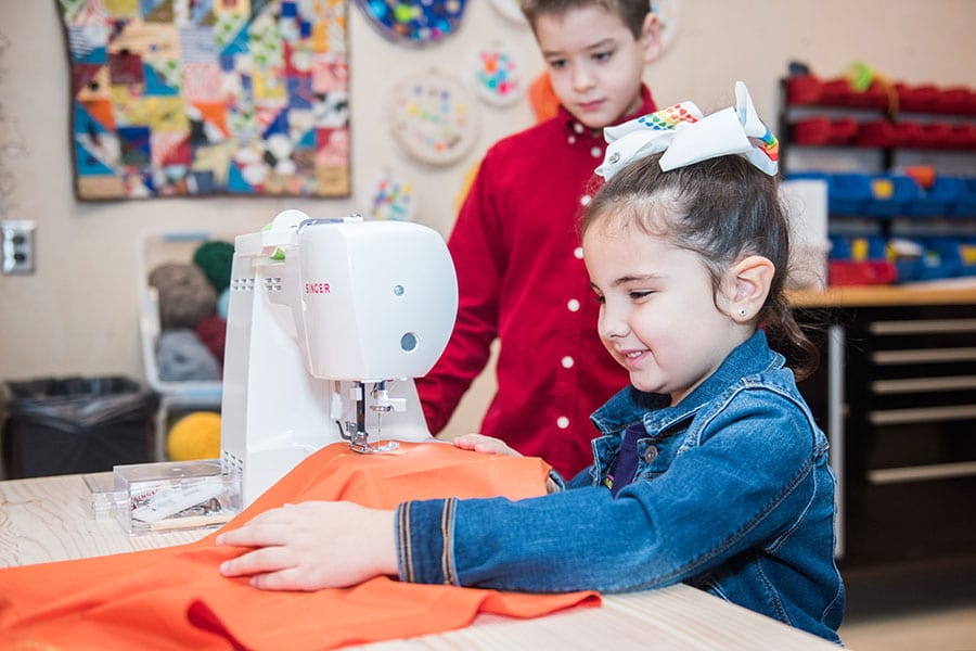children learning how to sew