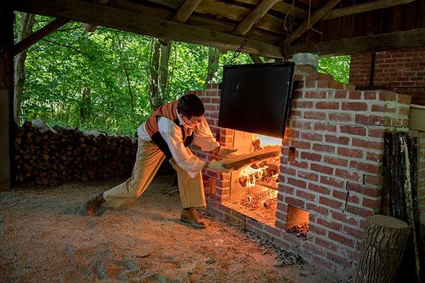 man feeding an outdoor fire oven