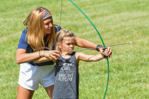 Camp counselor teaching camper how to aim a bow and arrow