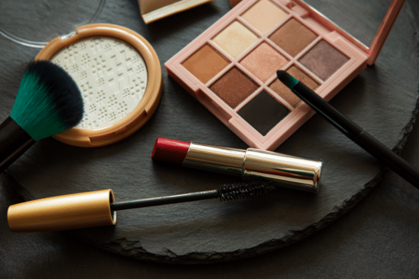 Eyeshow palette, lipstick and other makeup items laid out on a table