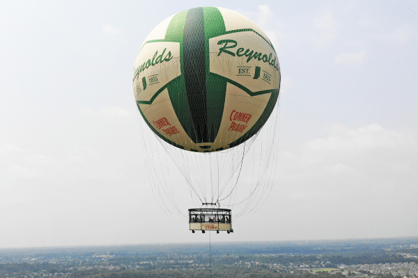 Aerial shot of new, green and white hot air balloon