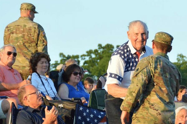 Military personnel shaking hands with veteran