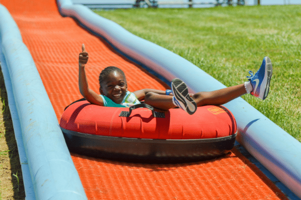 Girl Giving A Thumbs Up Going Down The Tubing Hill