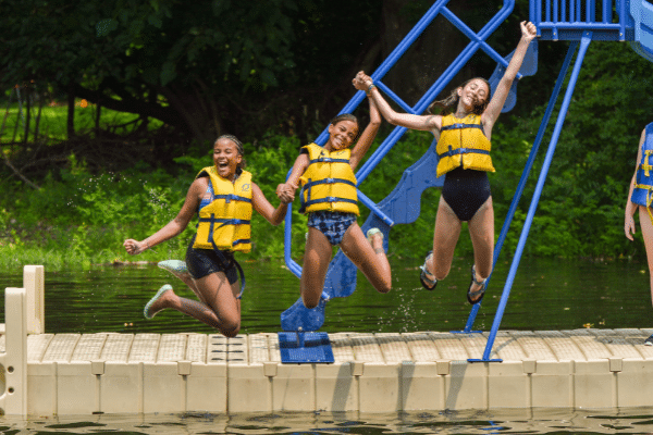 Three Campers Holding Hands And Jumping Off The Dock Into The Water