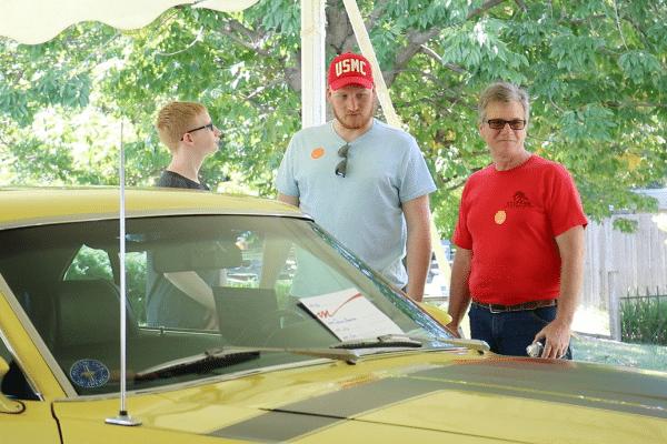 Three Men Looking At Yellow Vintage Car