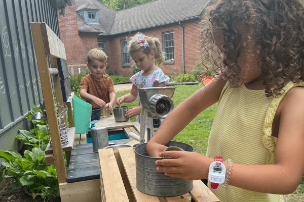 Preschool Students Playing In Pretend Kitchen