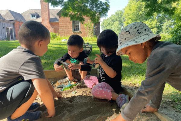 Preschool Students Playing In Sandbox