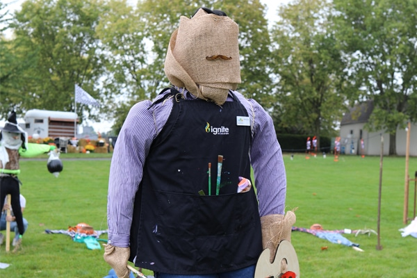 Scarecrow dressed in painters apron with paint brushes in hand