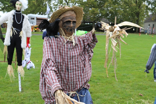 Spooky scarecrow with raven on its shoulder